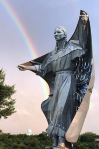 Dignity - statue of a Native American woman with a star quilt, overlooking the Missouri River in South Dakota, USA. A rainbow is in the sky above her.